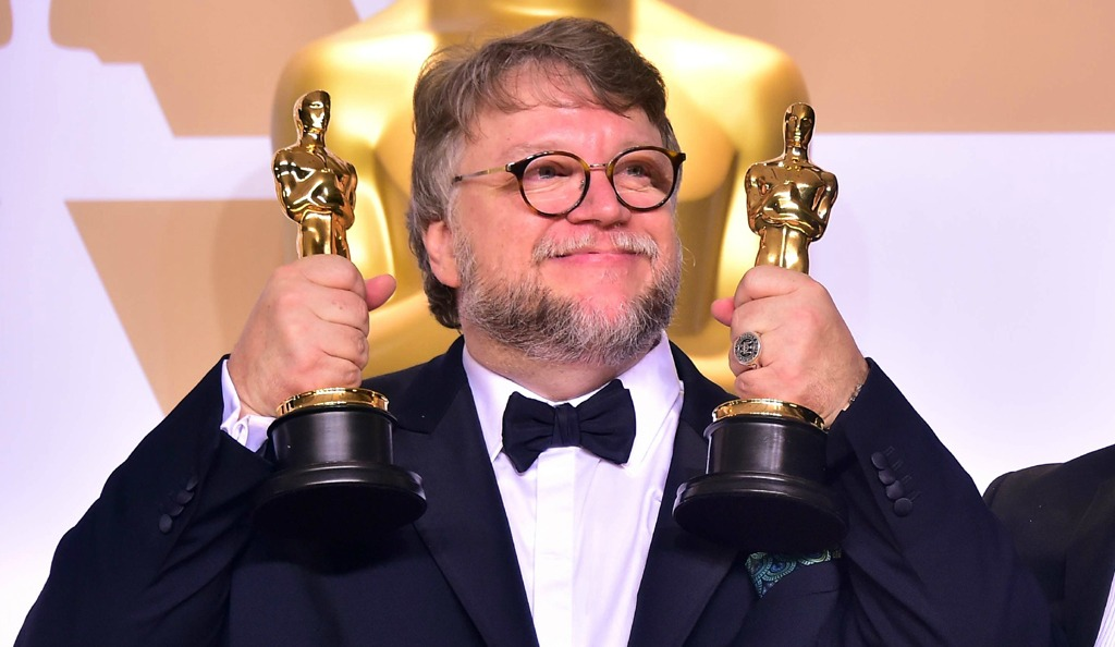 Director Guillermo del Toro, wearing black tux, holds up two golden Oscar trophies.