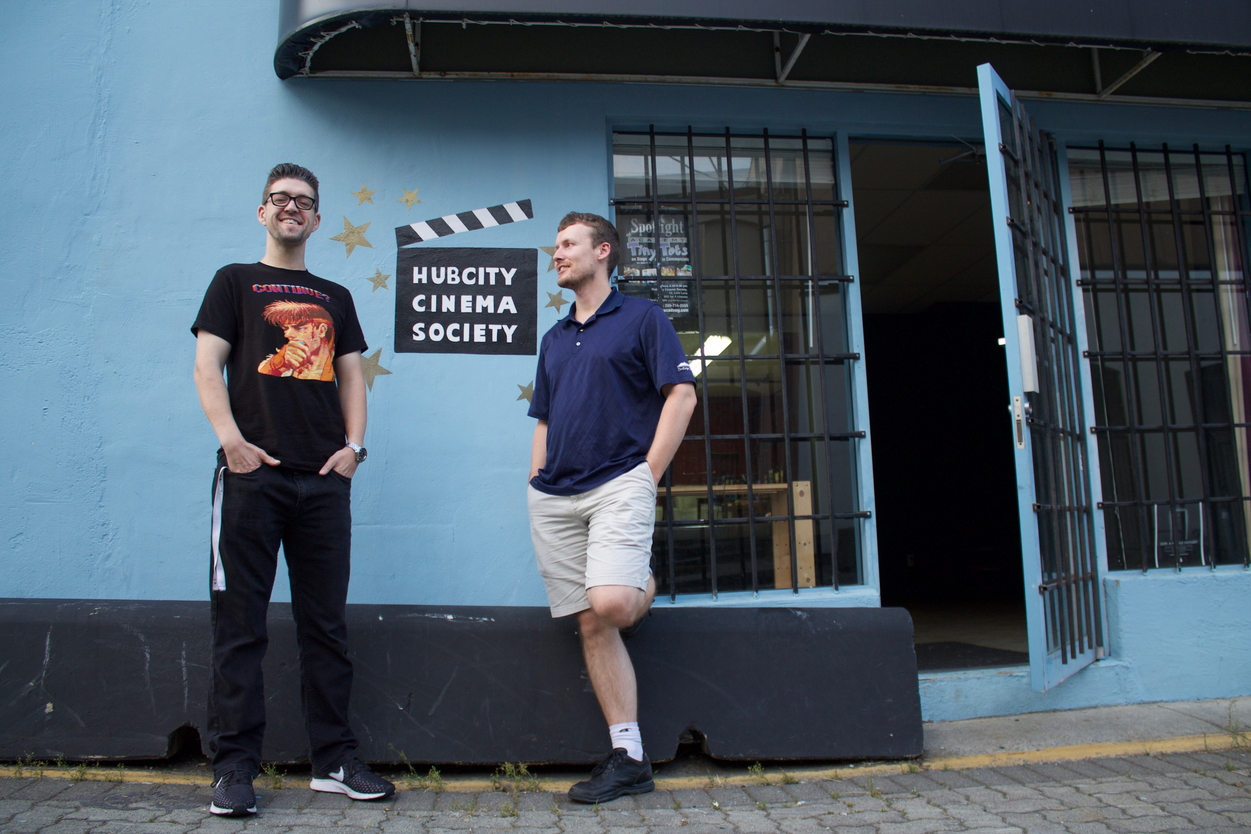 Two men stand a meter apart at the entrance of HCCS's headquarters. The door to society is open while both men entertain each other; the logo of the nonprofit organization is painted on the wall and between both co-founders. The logo is a clapperboard with the name Hub City Cinema Society within it.