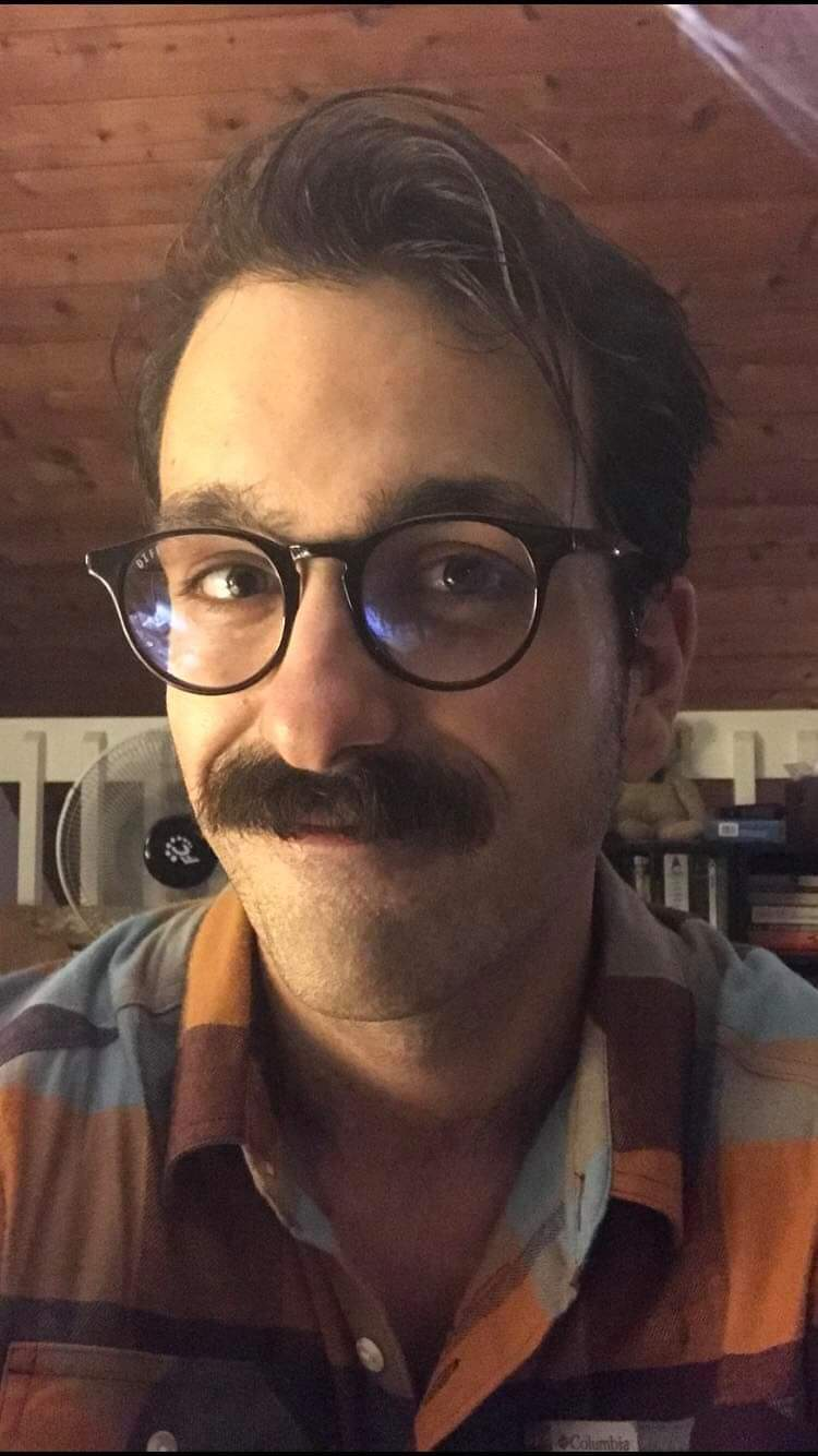 A portrait photo of the author. A Caucasian male wearing black frame glasses, sprouting a dark brown mustache, and smiling at the camera.