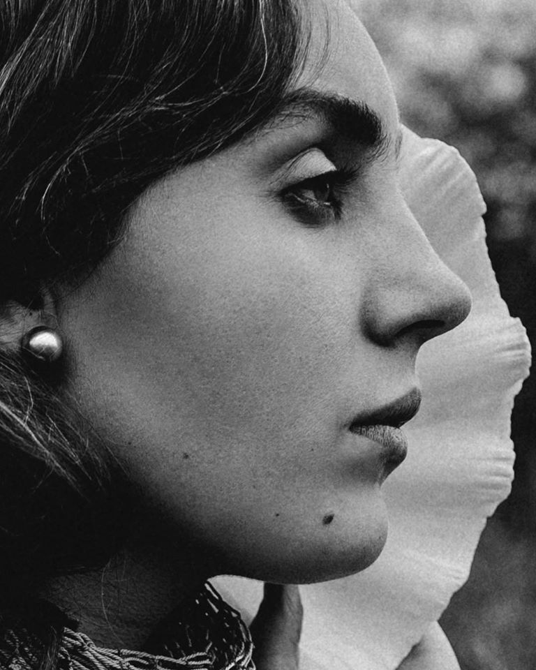 A side view/profile of a woman's face, filtered in black and white.
