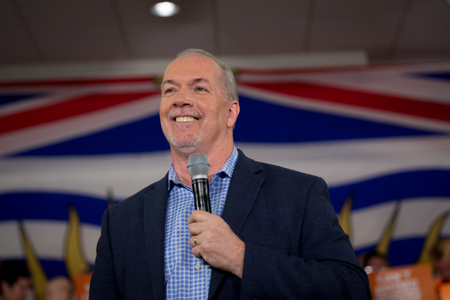 John Horgan smiling holding a microphone standing in front of a British Columbia flag