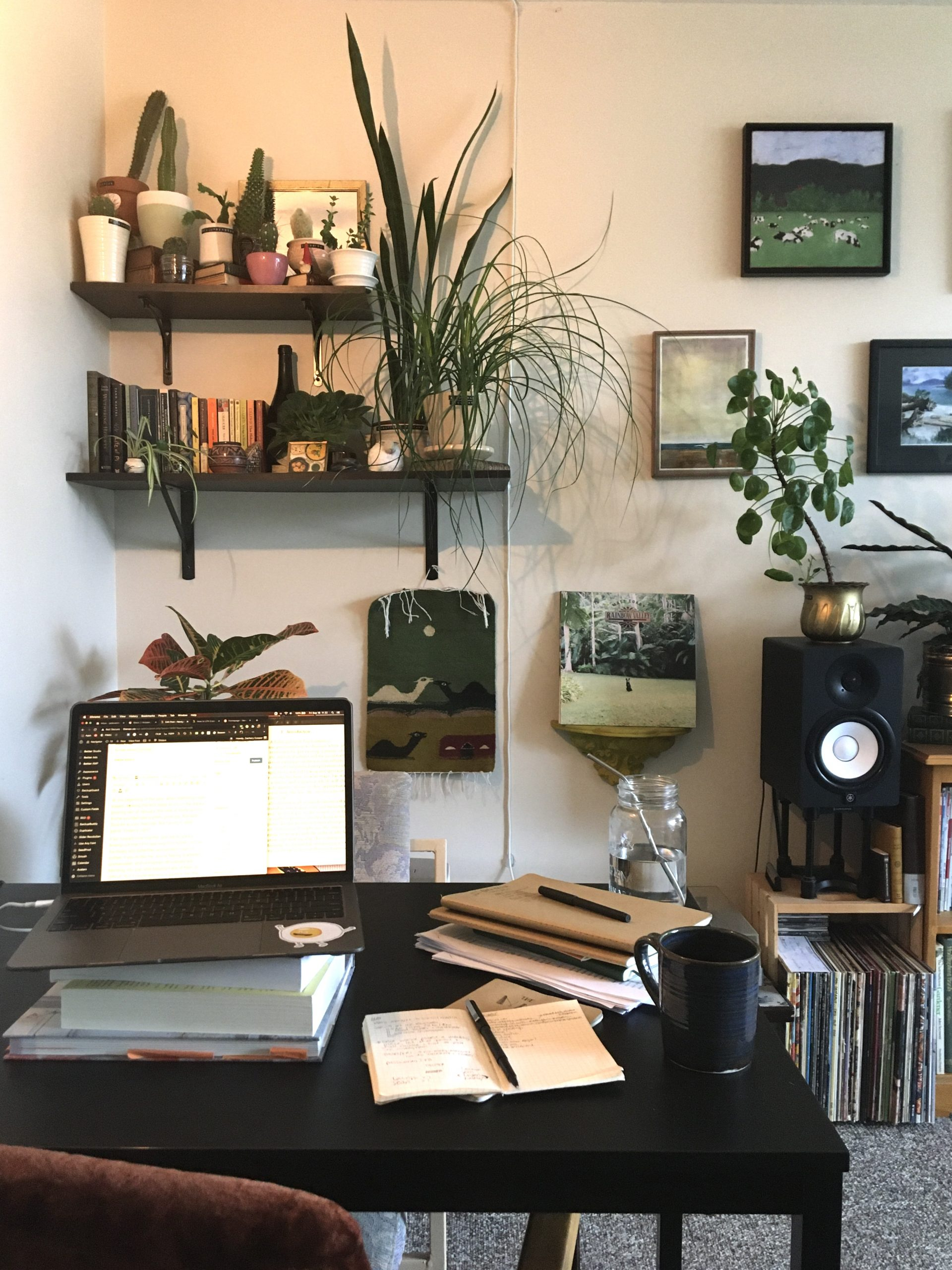 A laptop, notebooks, and mug of coffee sit on a desk in front of a wall of plants and books