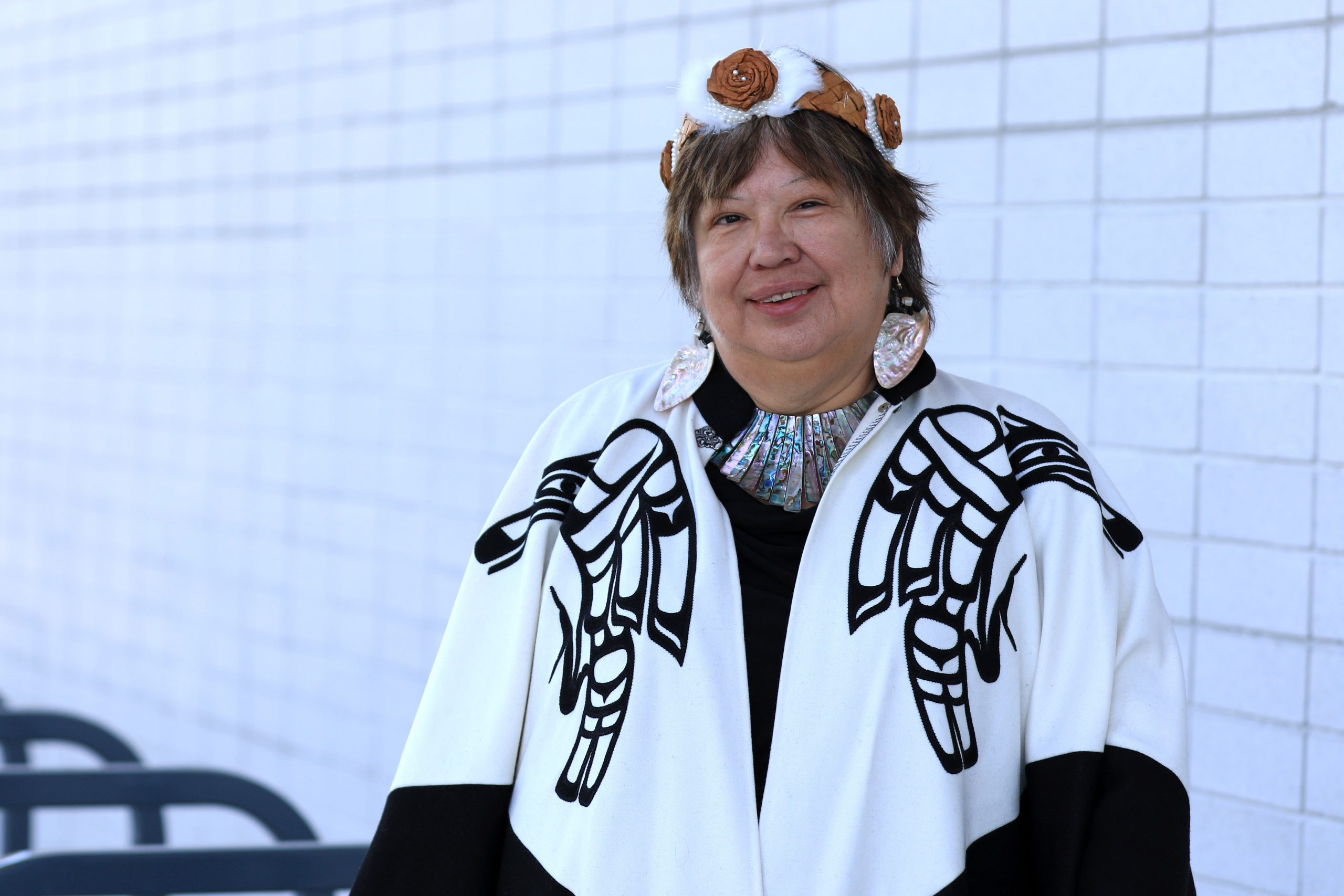 An Indigenous woman stands in traditional wear against a white background