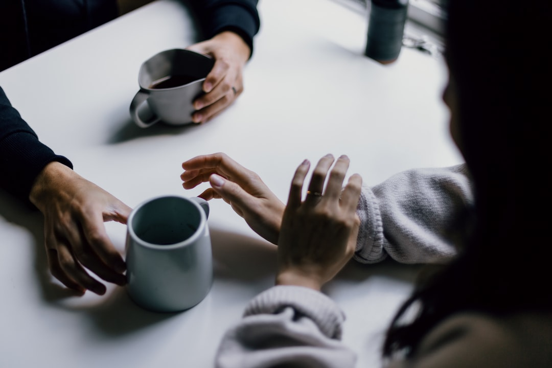 Two people across from one another at a table hold a mug of coffee