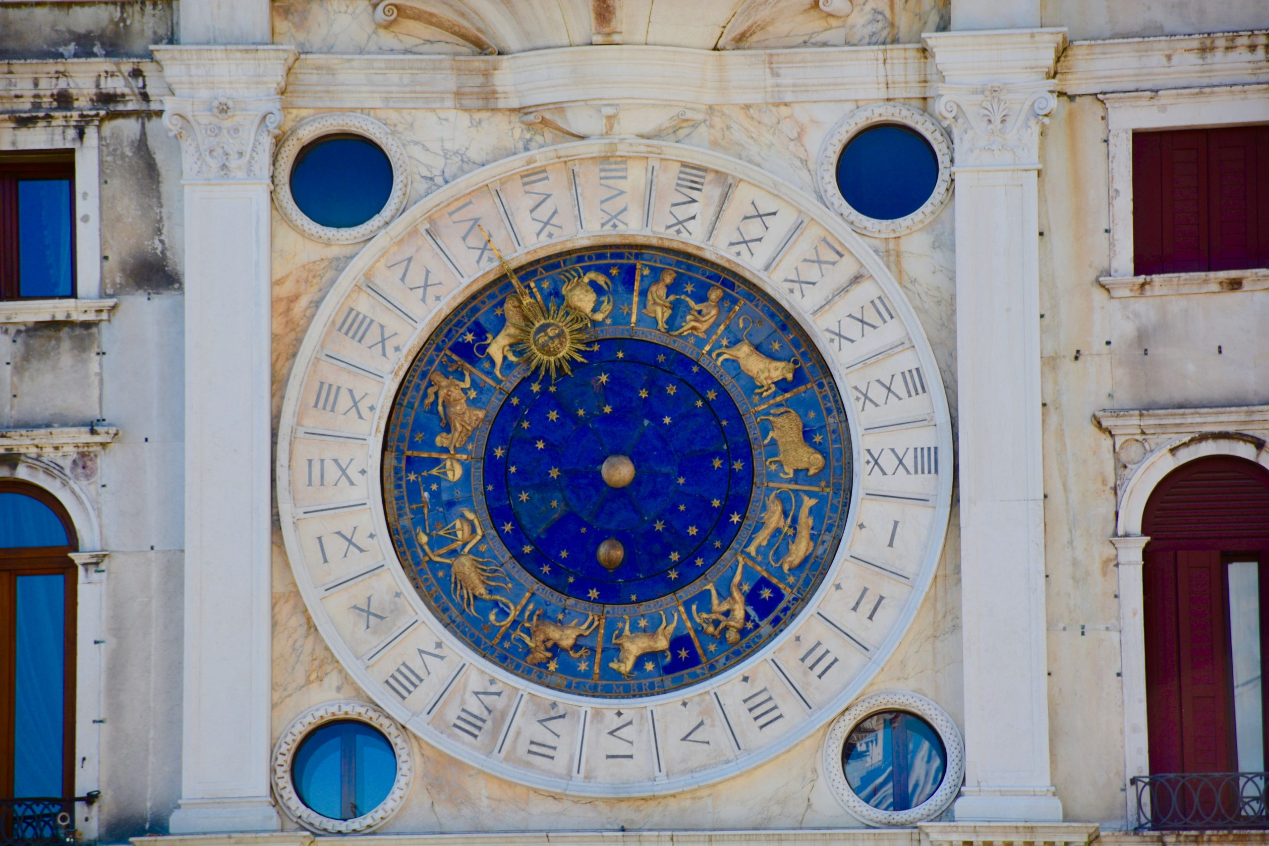a blue and gold horoscope calendar is carved into an old beige Italian stone building