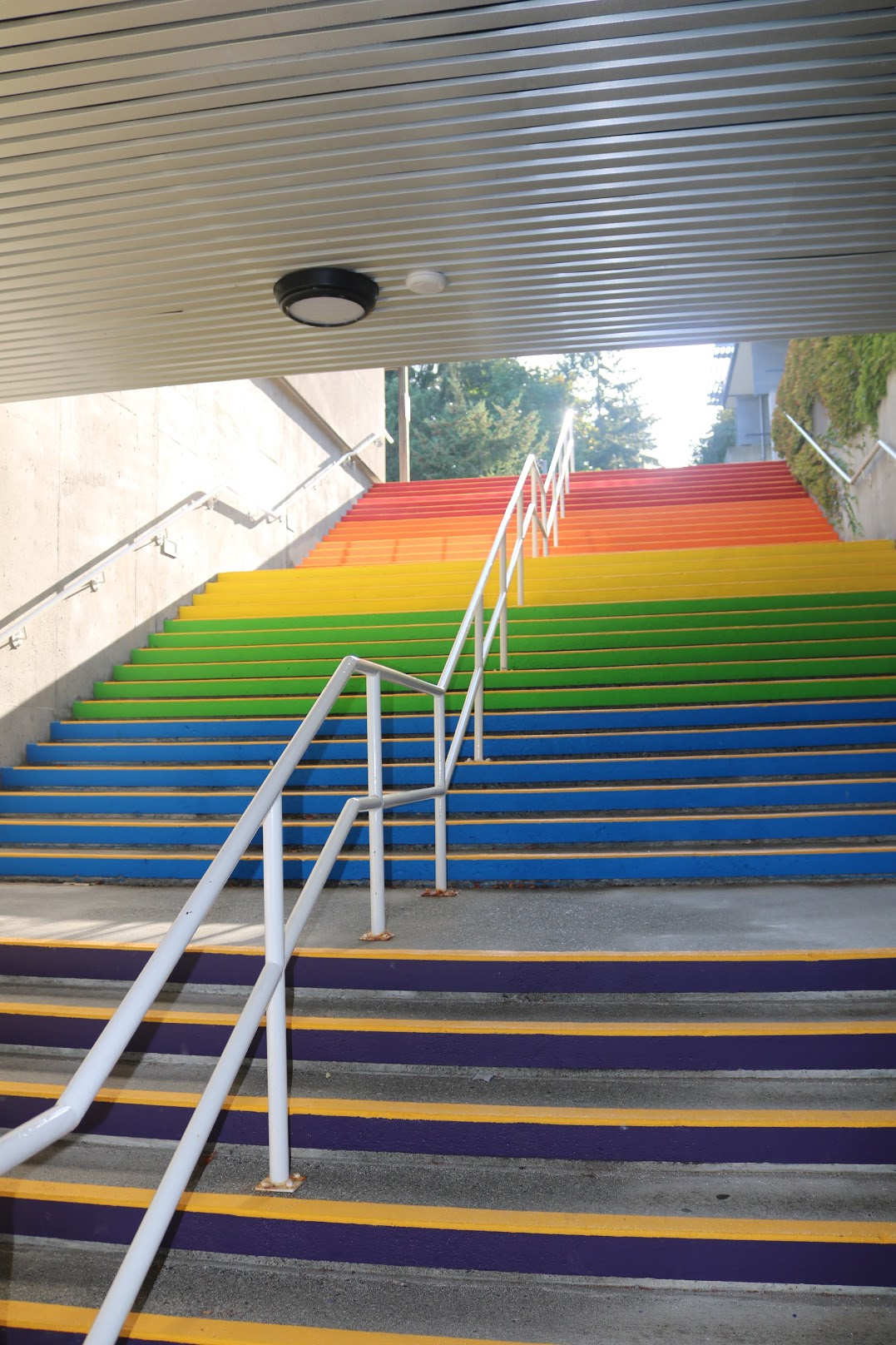 The photo shows the brightly coloured rainbow stairs that can be found on the Nanaimo campus of Vancouver Island University. The coloured steps go blue, green, yellow, orange, and then red up the stairs.