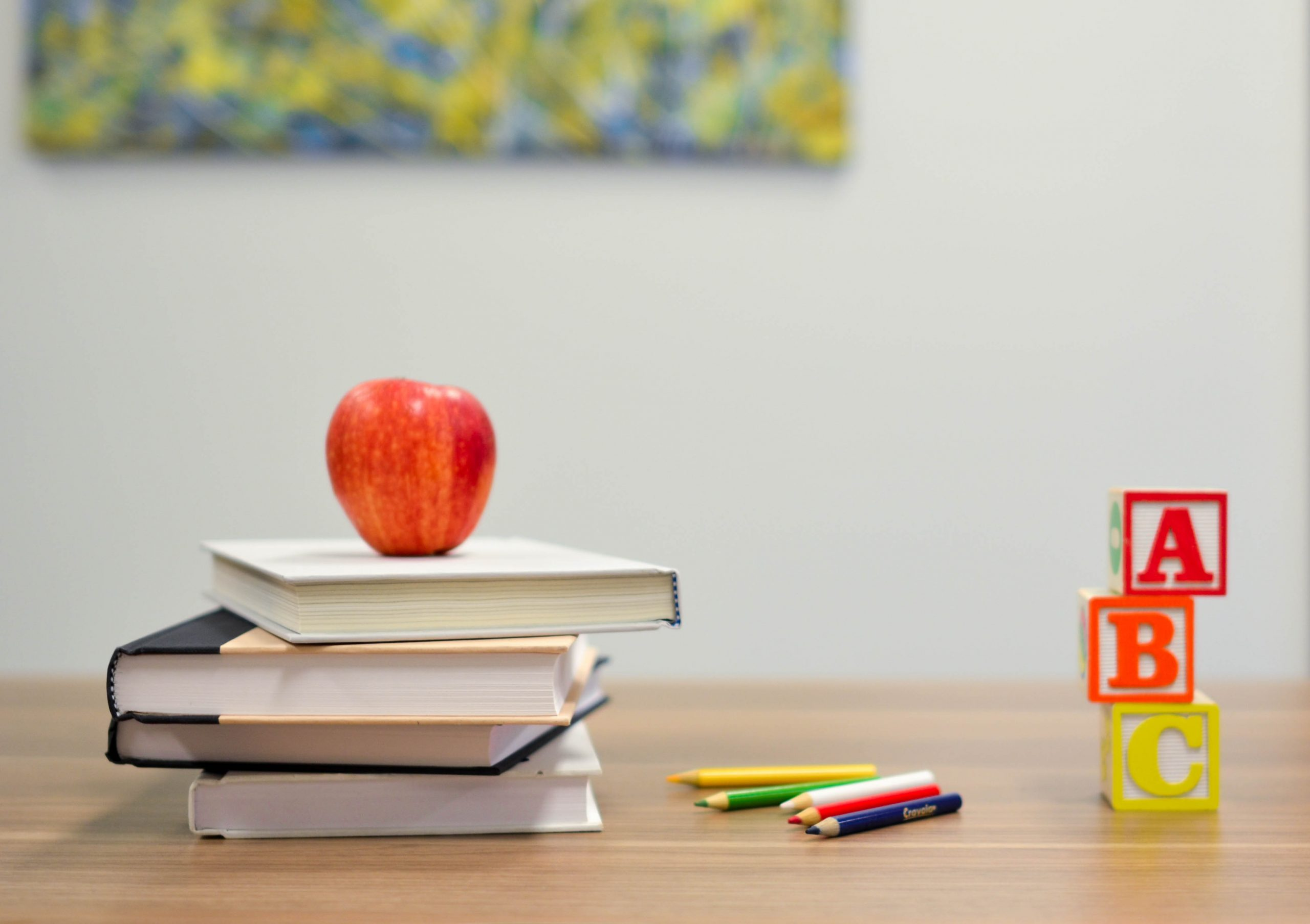 A teachers desk-top in a classroom. An apple sits on top of a stack of books next to some pencil-crayons and a tower of three alphabet blocks.