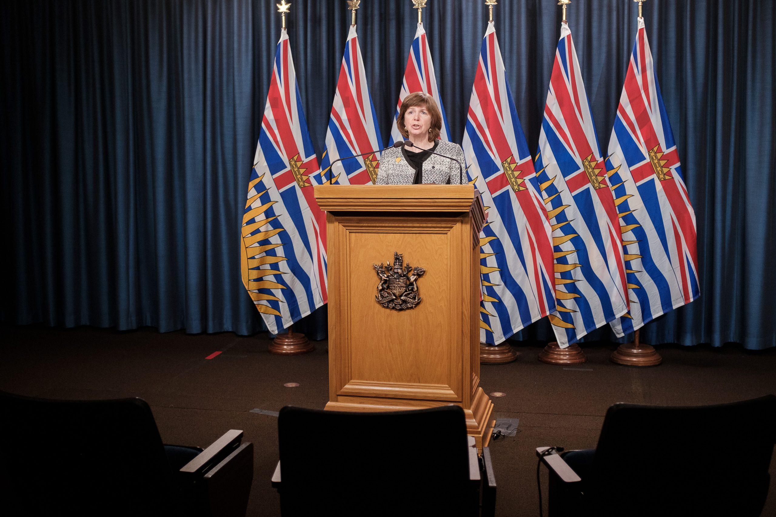 Sheila Malcolmson stands at a wooden podium in front of six British Columbia flags