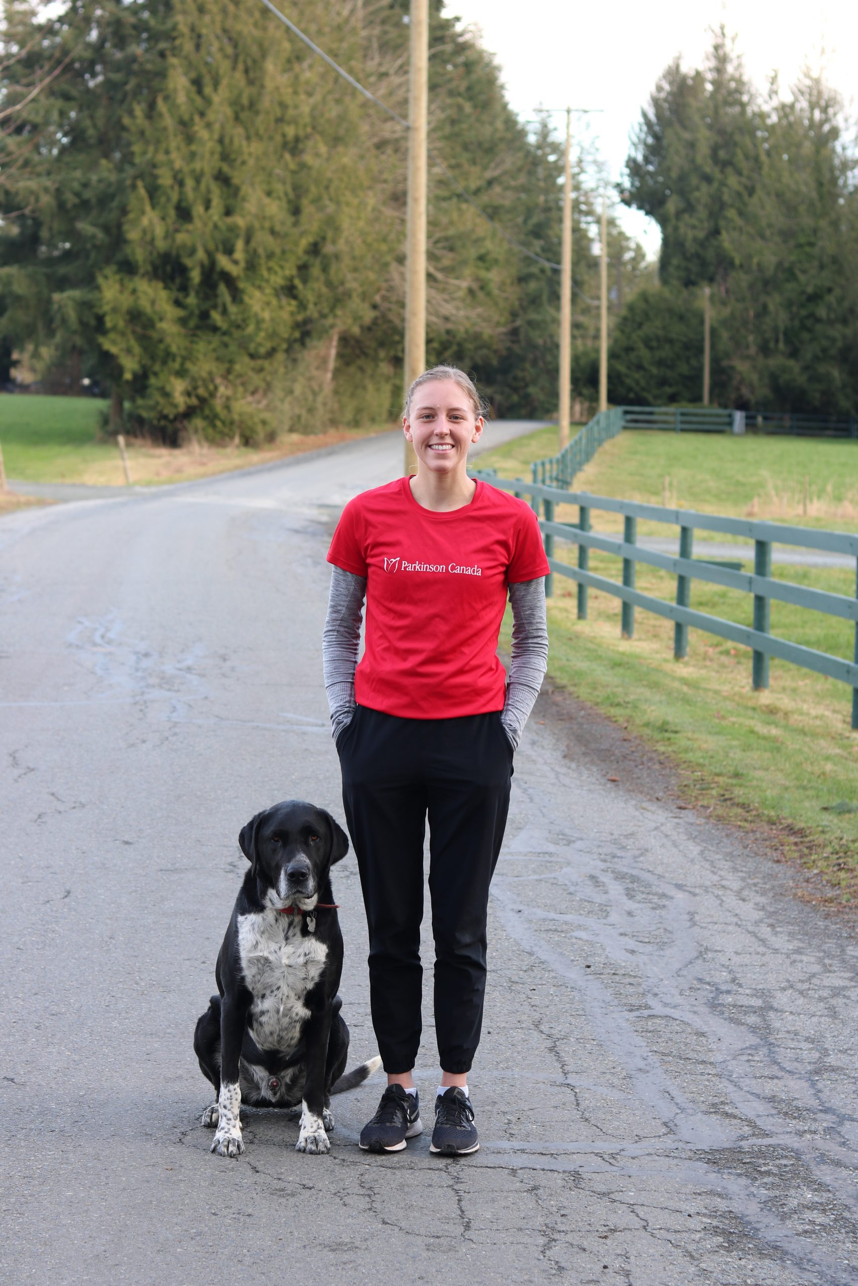 Danielle Groenedijk wearing black leggings and a red shirt reading 'Parkinson Canada' standing on the road beside a grassy field beside her medium height, balck and white dog, Bo