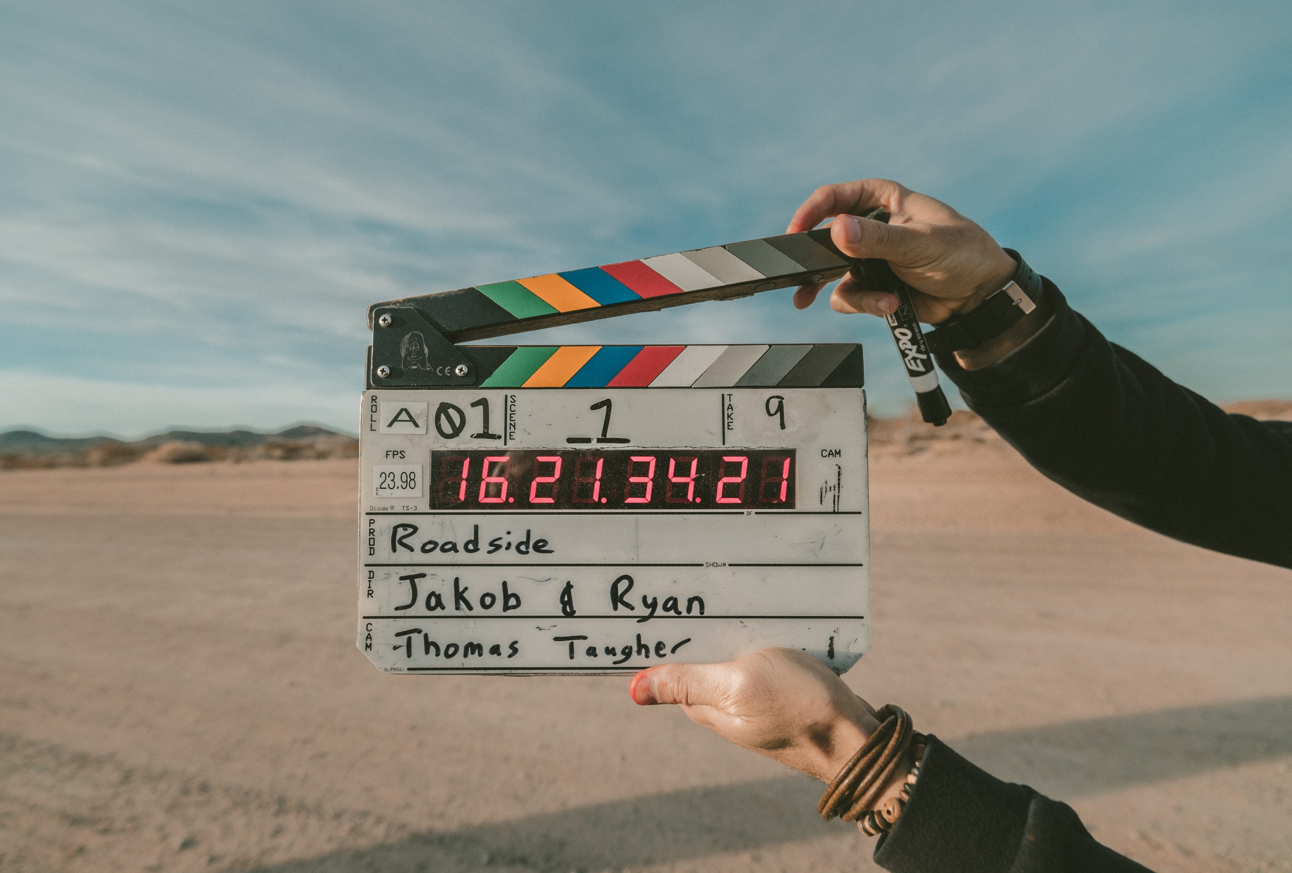 """In a desert, a man holds a film clapperboard that reads """"roadside, Jakob & Ryan, Thomas Taugher."""" The man is about to clap the clapper."""