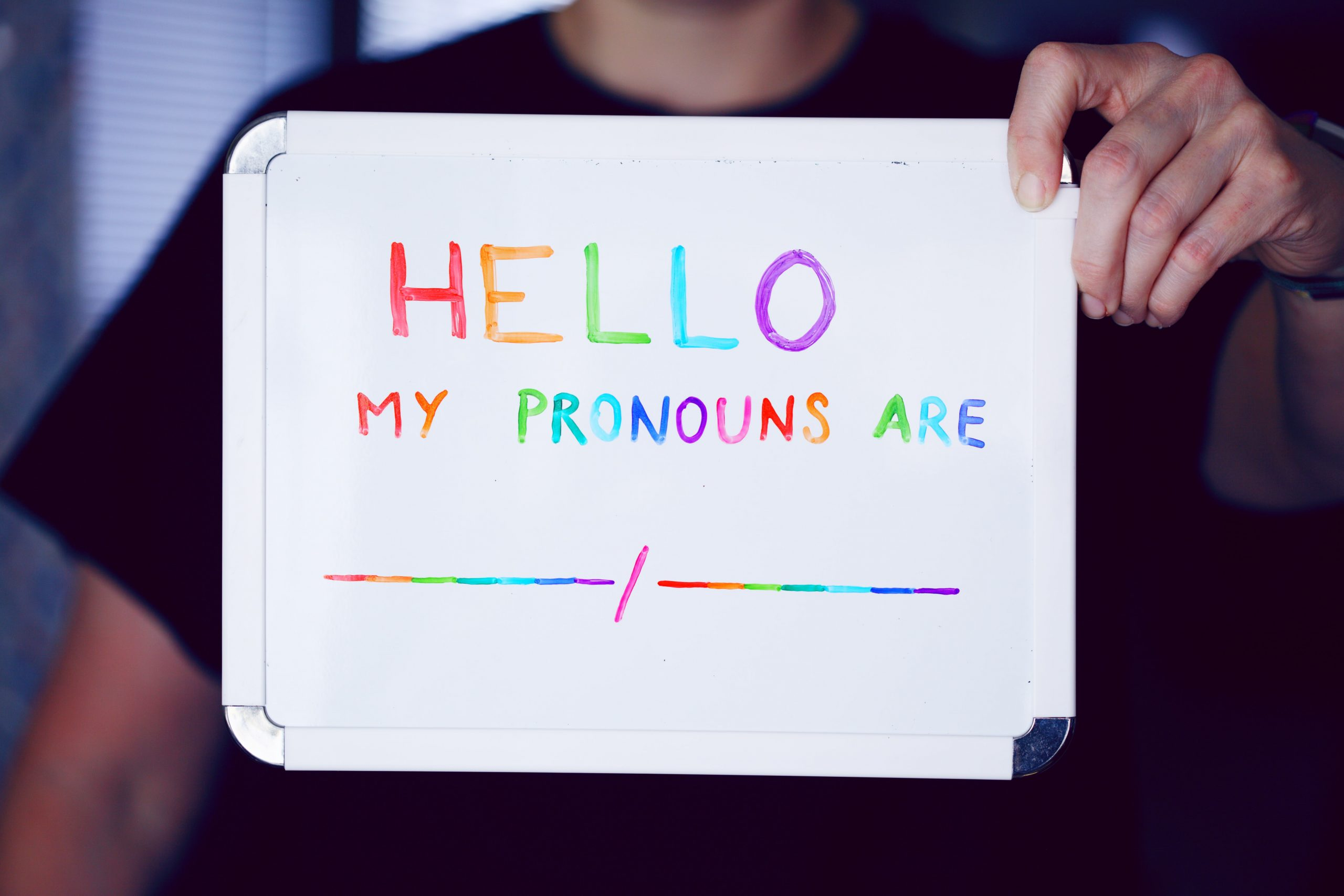 """A person holds a whiteboard that reads """"Hello my pronouns are"""" followed by two blank spaces. The words are rainbow coloured."""