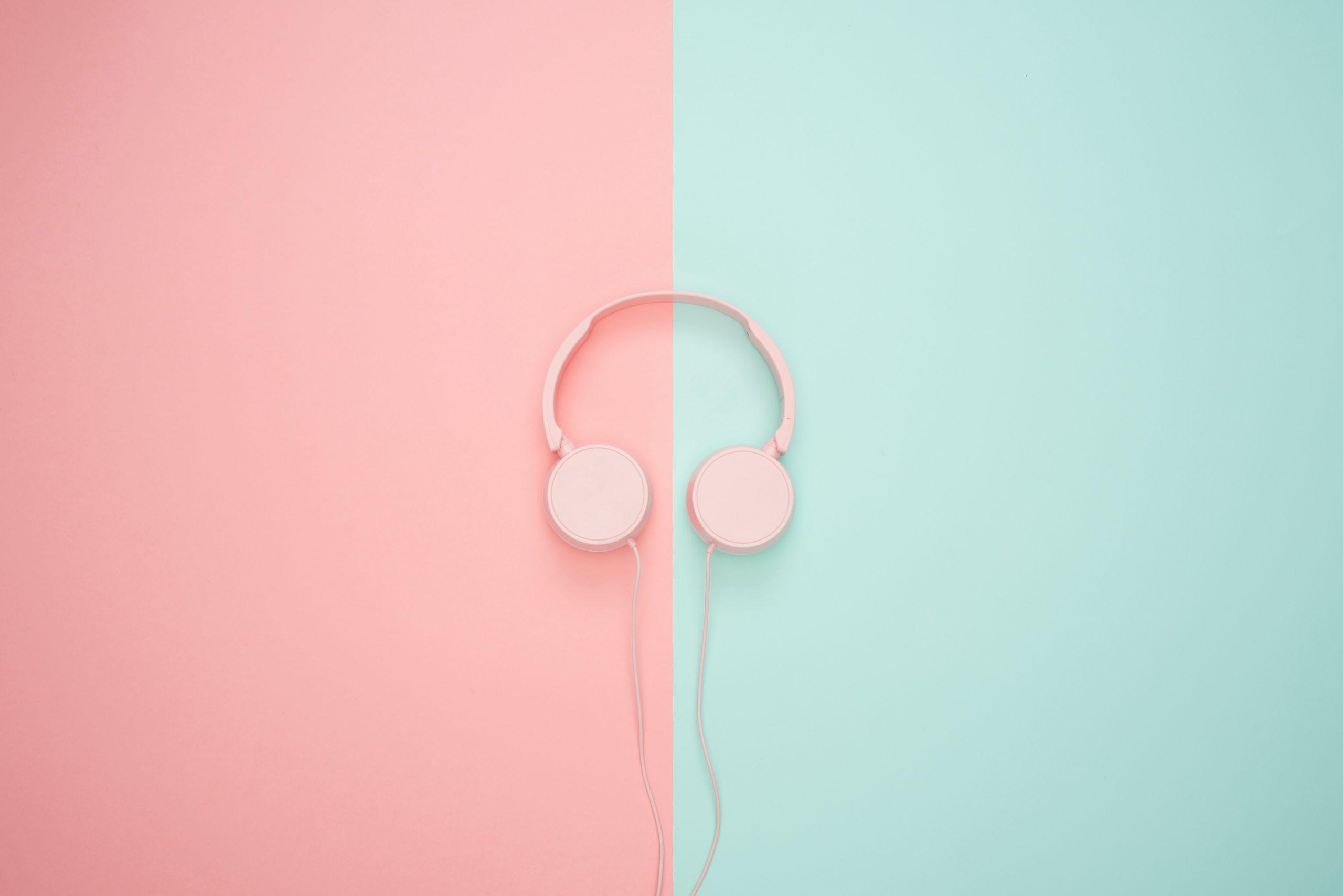 A pair of pink headphones lays on a half-pink half-blue floor