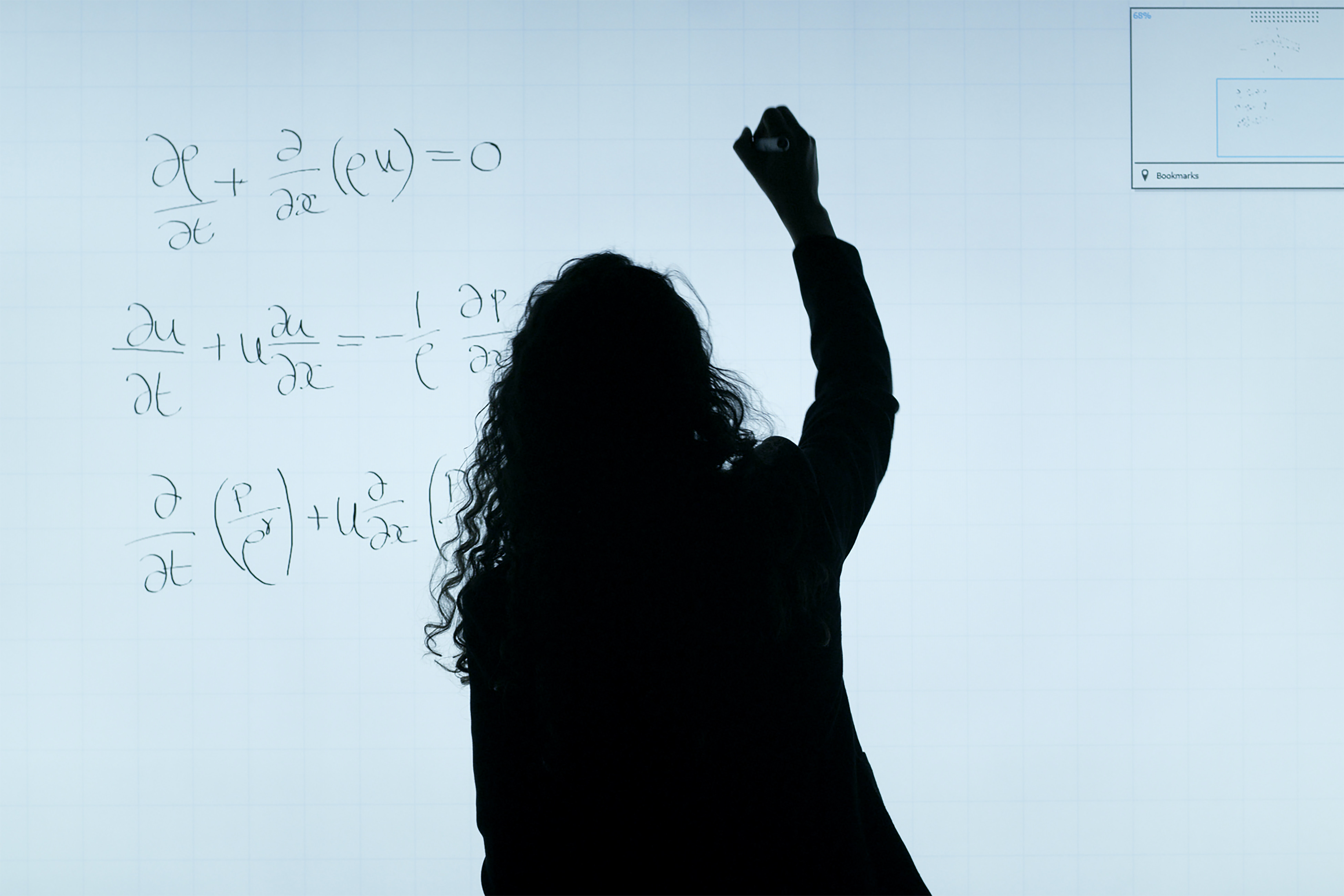 A black silhouette of a women writes a science formula on a whiteboard