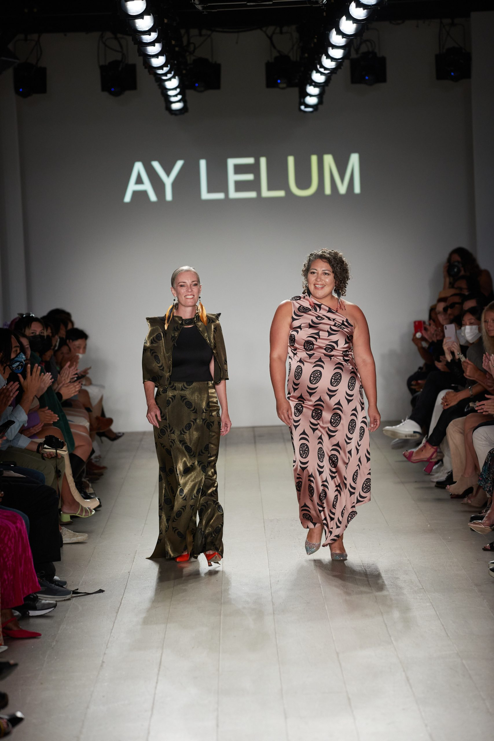 Aunalee Boyd-Good and Sophia Seward-Good stand at the end of the runway at their New York City showcase. Their brand name Ay Lelum is written behind them
