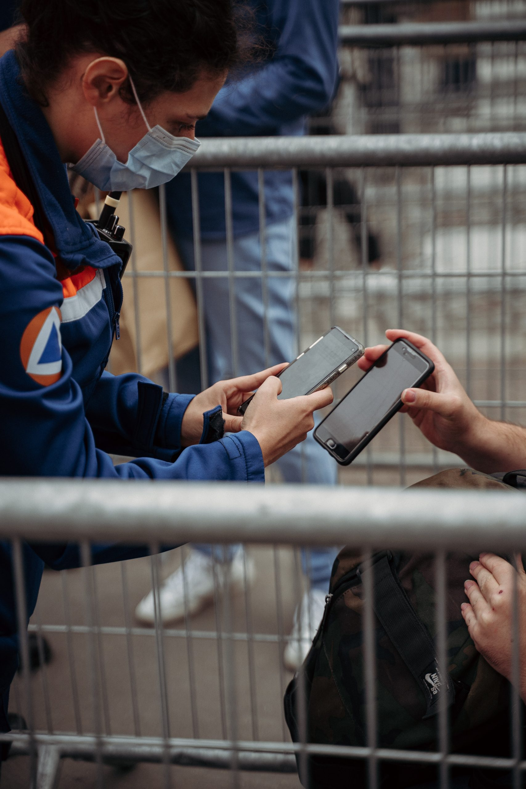 A person scans a cellphone screen offered by another.
